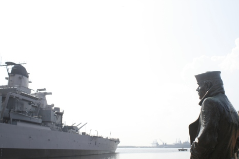 """Atop the Elizabeth River, the USS Wisconsin Battleship sits solemnly, like a patriarch bidding farewell to the sons and daughters departing across international waters for somebody else's home."""