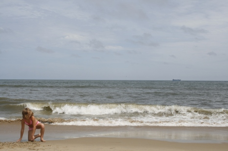 Young girl at beach, with incoming ship in the background